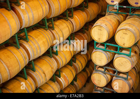 Stacks of wooden barrels holding aging wine at a vineyard cellar at Clos LaChance Winery in San Martin, California - Stock Photo