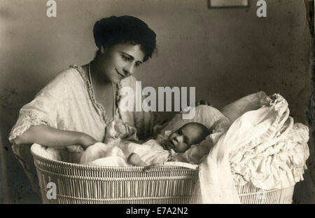 Woman Sitting next to Infant in Bassinet, Portrait, circa 1920 - Stock Photo