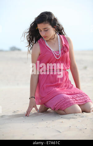 Young 12 year old teen in red dress on the beach. Model released - Stock Photo
