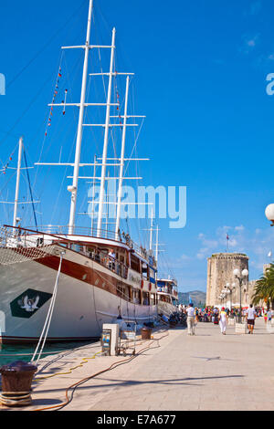 Croatia, Trogir: tourists on the sea promenade with touristic cruise ships moored and the view of the tower of Kamerlengo - Stock Photo