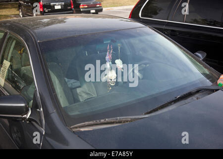 A skull and various other ornaments hanging from the rear view mirror of a car - Stock Photo