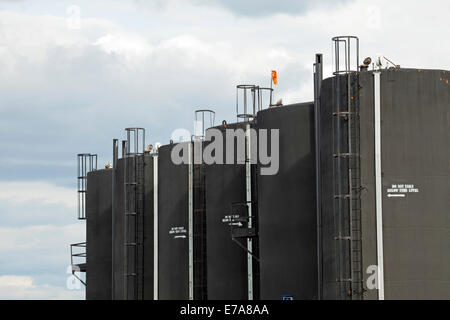 Row of oil storage tanks for cold heavy oil production with sand (CHOPS) against overcast sky,  Alberta, Canada - Stock Photo