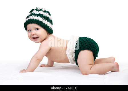 Happy baby boy in knitted hat crawling over white background - Stock Photo