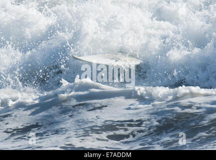 Surfboard appearing from waves after surfer has wiped out - Stock Photo