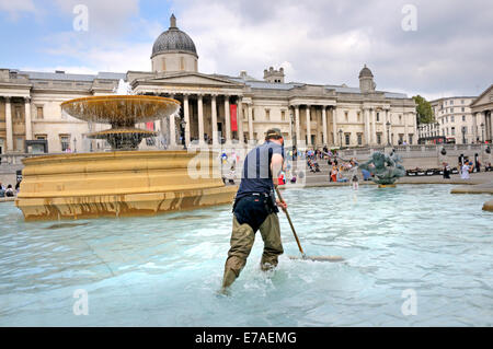 London, England, UK. Man sweeping the fountains in Trafalgar Square - Stock Photo