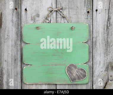 Blank green sign with wooden heart hanging on old weathered wood door - Stock Photo