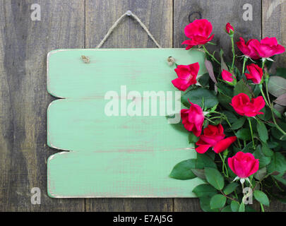 Distressed blank green sign with flower border of red roses hanging on rustic wood background - Stock Photo