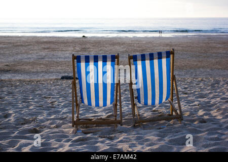 Two deck chairs on Porthmeor beach at sunset, St Ives, Cornwall, England, UK - Stock Photo