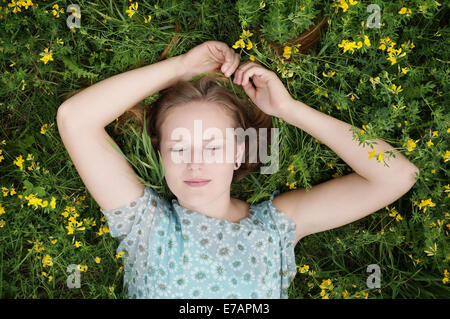 young woman sleeping in a flower meadow - Stock Photo