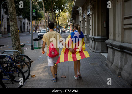 Barcelona, Spain. 11th Sep, 2014. A couple carrying an independentist catalan  flag walks the streets of Barcelona. - Stock Photo