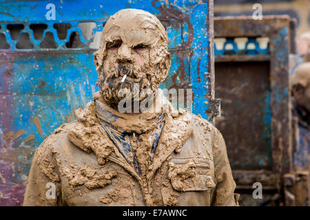 Shiite Muslim man, completely covered with mud, smoking a cigarette, on Ashura Day, in Bijar, Iran. - Stock Photo