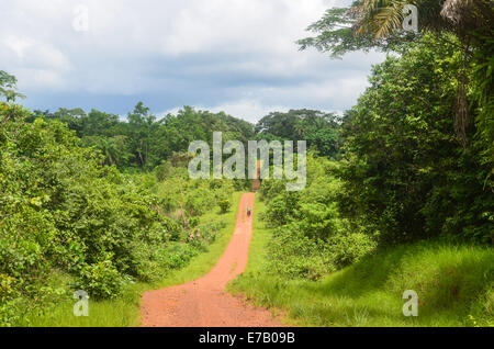 Travelling on the red earth dirt roads of eastern Sierra Leone to Liberia - Stock Photo