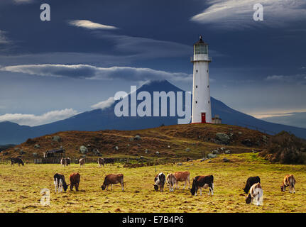 Cape Egmont Lighthouse and Taranaki Mount on background, New Zealand - Stock Photo