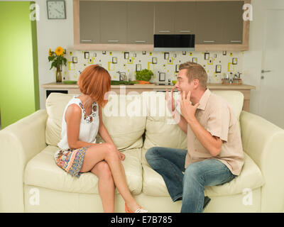 young caucasian man and woman sitting on couch and having argument - Stock Photo