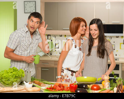 portrait of two beautiful caucasian women standing in kitchen cooking, laughing and whispering something, with one - Stock Photo