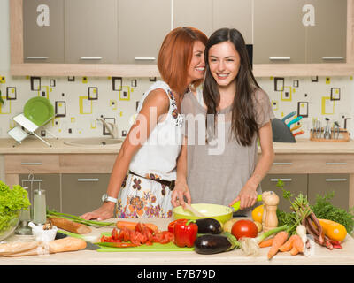 portrait of two beautiful caucasian women standing in kitchen and cooking, laughing, whispering something - Stock Photo