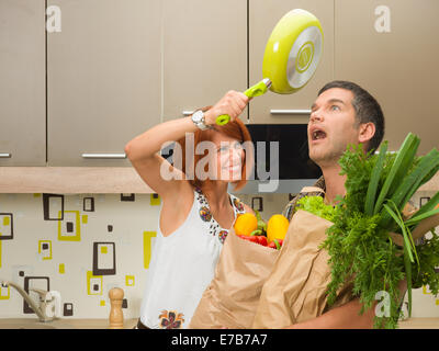 close-up of young woman hitting  surprised shocked man on head with frying pan, both standing in kitchen - Stock Photo