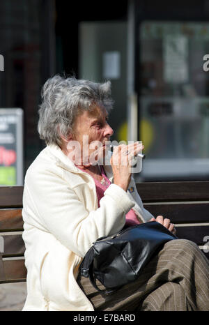 Elderly lady smoking an electronic cigarette - Stock Photo