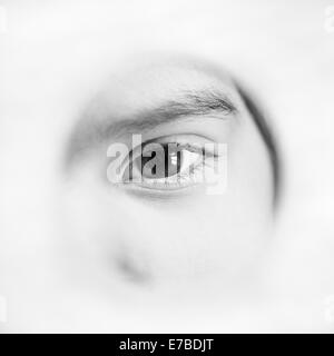 Eye of serious little girl peeking through hole - Stock Photo