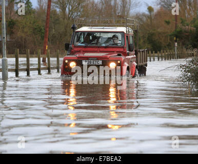 Residents of Burrowbridge, Somerset, use tractors and Land Rovers to get through the flood water that has risen - Stock Photo
