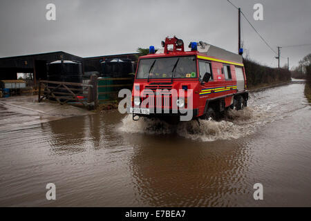 A fire service truck drives through Thorney, Somerset. - Stock Photo