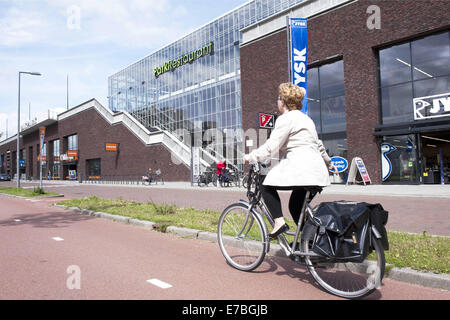 Rotterdam, South Holland, The Netherlands, Holland. 29th Aug, 2014. A woman cycles along a shopping center. On top - Stock Photo