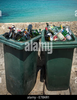 Discarded bottles of alcohol in dustbins by the sea. - Stock Photo