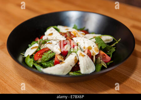 Fresh salad in a black bowl on a wooden table with rucola, cherry tomtoes, mozzarella cheese, balsamico vinegret, - Stock Photo