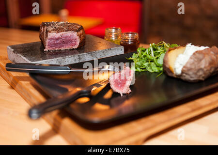 Rare or medium rare steak, T-bone, sirloin on a stone with baked potato with curd  with sauce ans rucola on a wooden - Stock Photo