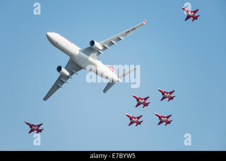 PAYERNE, SWITZERLAND - SEPTEMBER 6: Flight of Airbus A-330 of Swiss Airlines followed by Patrouille Suisse aerobatic - Stock Photo