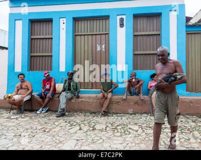 man in street walking with iguana, Trinidad, Cuba - Stock Photo