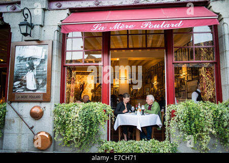 French people person couple tourists eating at outdoor restaurant in Abbey Mont Saint Michel,  France - Stock Photo