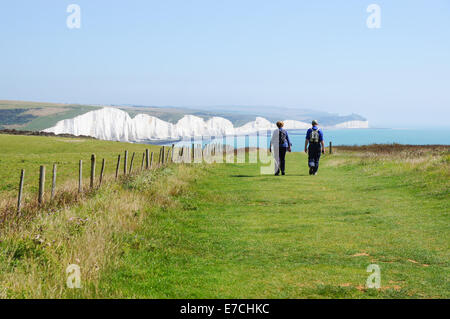 Walkers striding towards the Seven Sisters chalk cliffs near Seaford East Sussex England United Kingdom UK - Stock Photo
