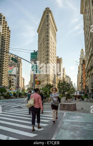 elegant profile of 1902 Flatiron building dominates skyline towering over pedestrians at intersection of Broadway - Stock Photo