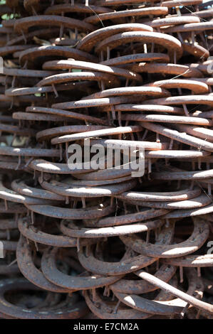 Old & used horse shoes piled up as a modern statue in an artisan shop in Los Alamos, California - Stock Photo