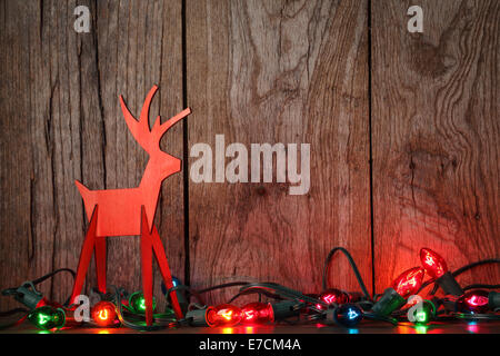 Christmas lights on wooden background with wood deer - Stock Photo