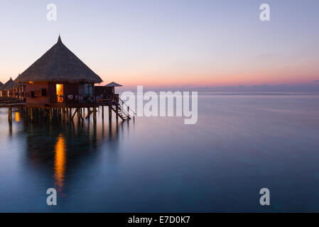 Panorama of tropical island resort with over-water bungalows at night. Maldives. Ari Atoll.  Scenic sunset over - Stock Photo