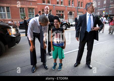 US Secret Service agents keep watch as President Barack Obama greets a young boy on the street July 8, 2014 in Denver, - Stock Photo