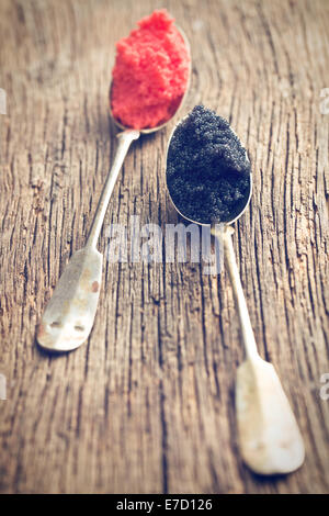 black and red caviar in spoon on wooden table - Stock Photo