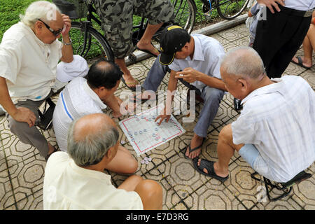 Men play a board game on a street in Hanoi, Vietnam. - Stock Photo