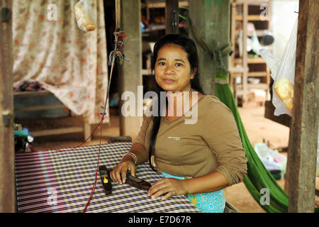 A woman at her loom in Chong Koh, Cambodia. The village is known for its weaving. - Stock Photo