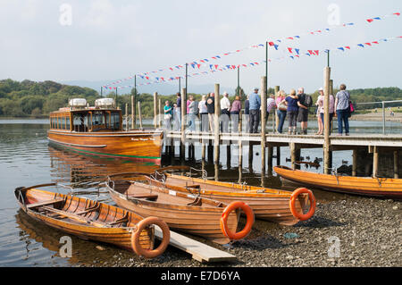 Rowing boats, lake launch and people waiting on Keswick pier, Allerdale, Cumbria, England, UK - Stock Photo