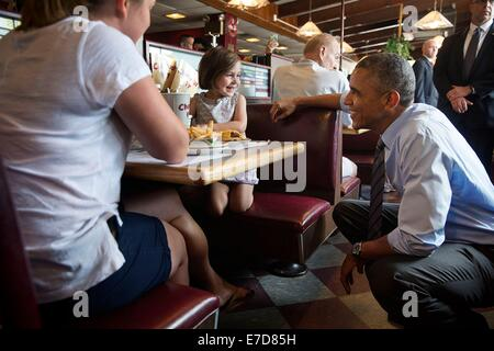 US President Barack Obama talks with a little girl at the Charcoal Pit restaurant July 17, 2014 in Wilmington, Delaware. - Stock Photo