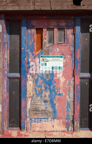 A very old derelict door with a sign talking about a restoration project in the works in downtown, Caledonia,  Ontario, - Stock Photo