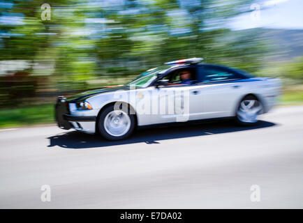 Pan motion blur view of speeding Colorado State Police car, central Colorado, USA - Stock Photo