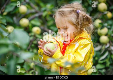 Little girl in the apple garden - Stock Photo