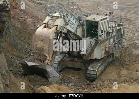A massive Liebherr face shovel excavator loads overburden soil in a large African open cast copper mine. - Stock Photo