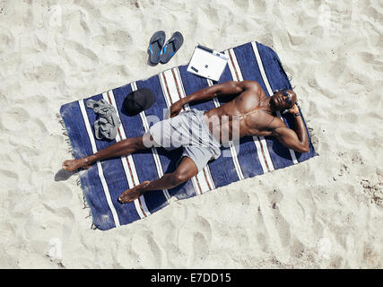 Top view of muscular young man sunbathing on beach. African guy wearing sunglasses and listening to music on headphones - Stock Photo