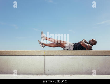 African young man doing stretching exercising while lying on a wall by walkway outdoors. Muscular young fitness - Stock Photo