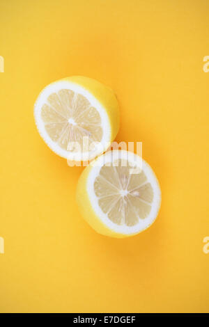 Fresh lemon cut in half on yellow background. - Stock Photo